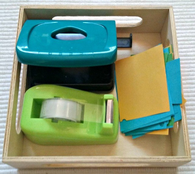 Whole puncher, construction paper and hole puncher.