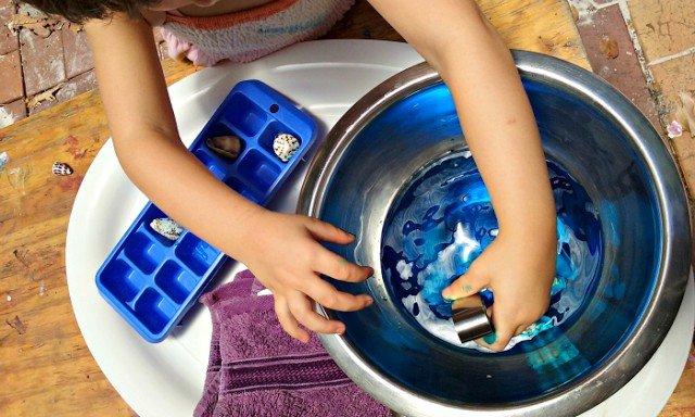 Child gathering shells with tongs for placing them in a ice black container.