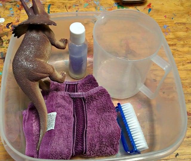 Washing toy station with towel, brush, jug, soap and dinosaur.
