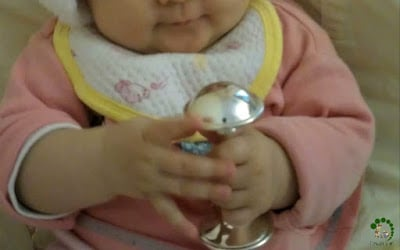 Baby holding a silver rattle