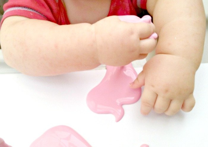 Baby playing with beetroot goop