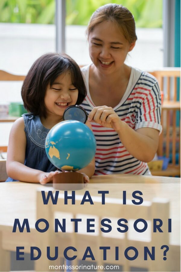 A child and a woman looking at a world Montessori globe through a magnifying glass.