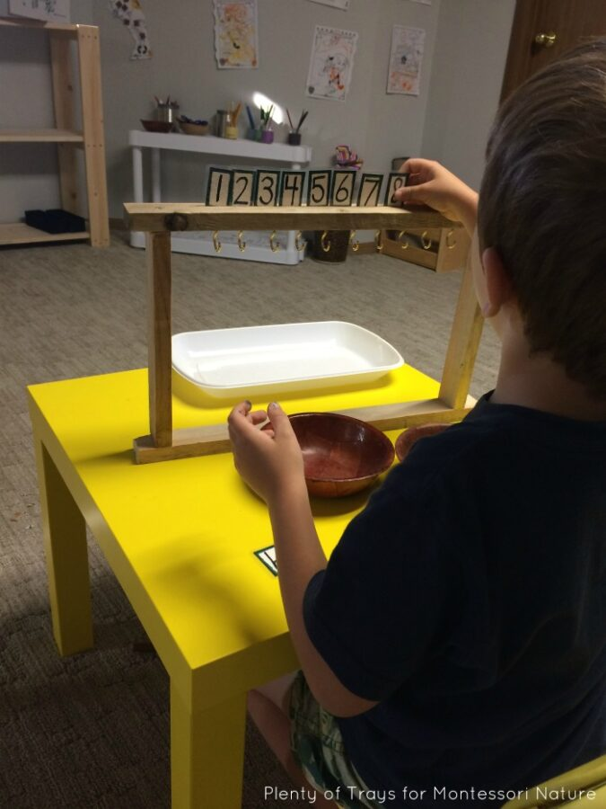 A boy working with number cards with a frame