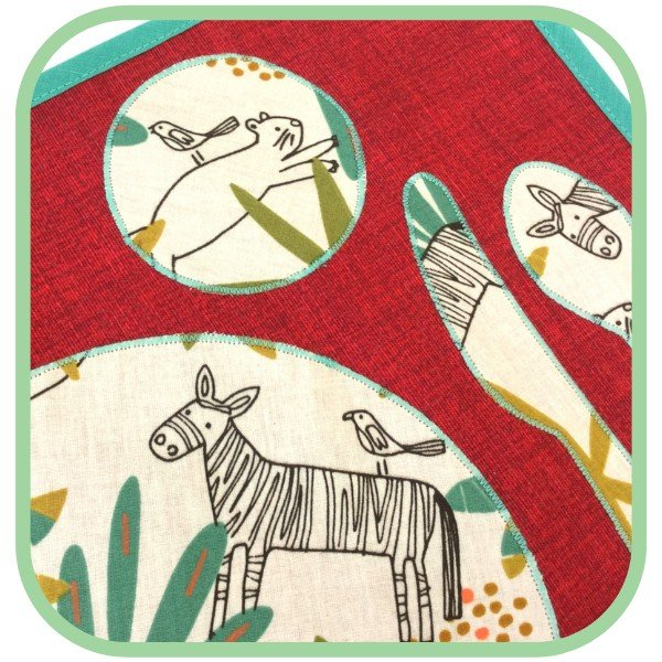 A red handmade placemat for little onces with patterns.