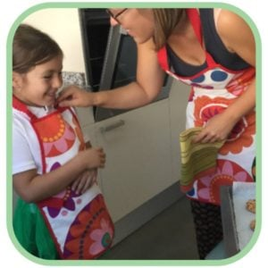 A woman talking to her daughter, both wearing waterproof aprons.
