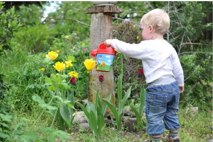 A toddler watering flowers in the garden