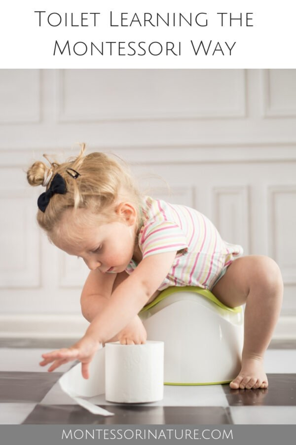 Child sitting on a potty holding a toilet roll with her fingers and unrolling it