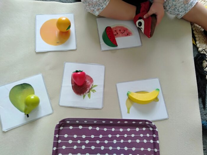 a child matching toys fruits to the images