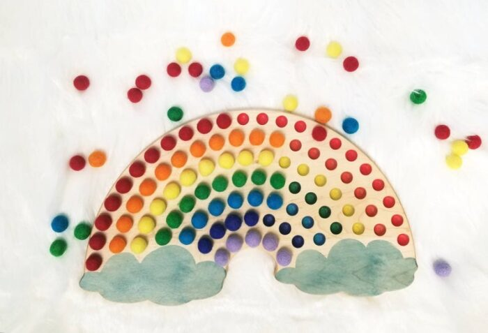 Wooden rainbow with felt balls of different colors for sorting colors