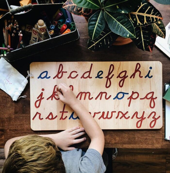 Wooden puzzle with cursive letters of the alphabet