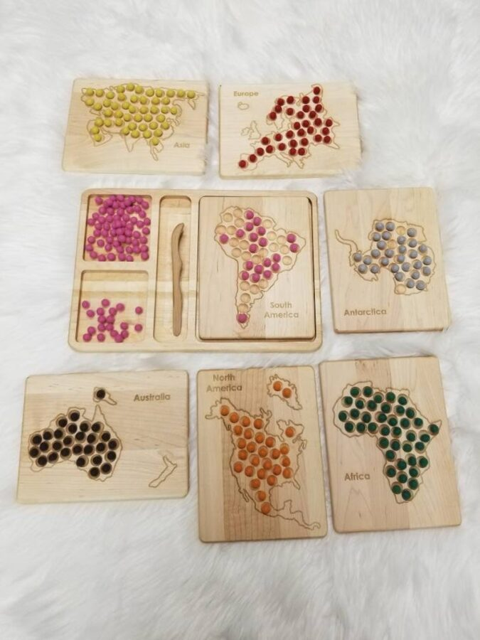 Wooden puzzles of the continents with woolen balls of different colors for sorting including tongs.