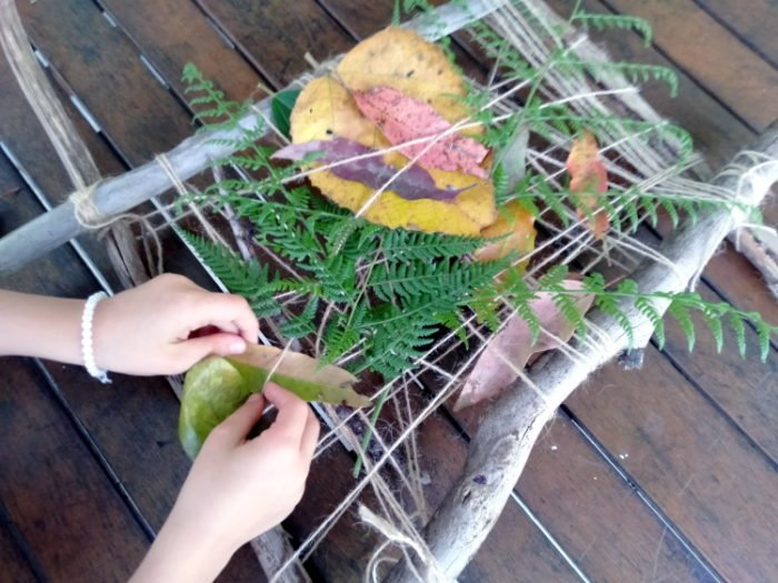 A girl weaving leaves into a weaving frame outdoors