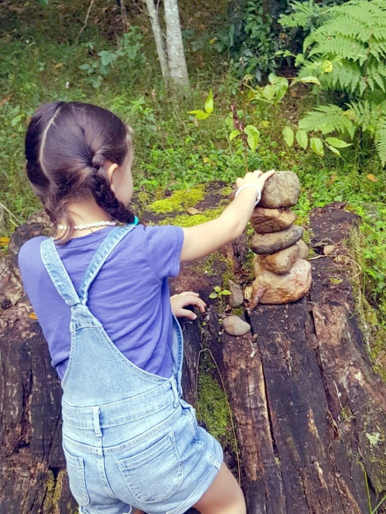 A girl stucking up rocks outdoors