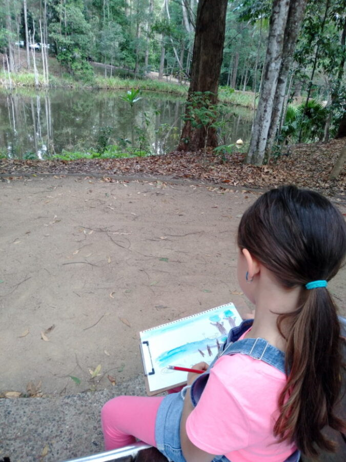 A girl making a drawing of a pond outdoors