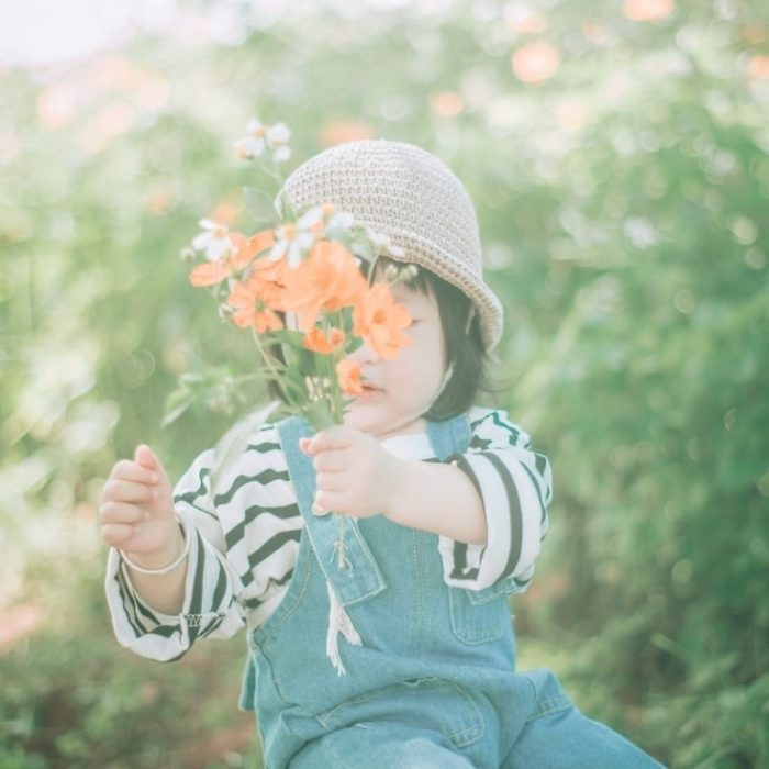 A toddler holding a bunch of wildflowers