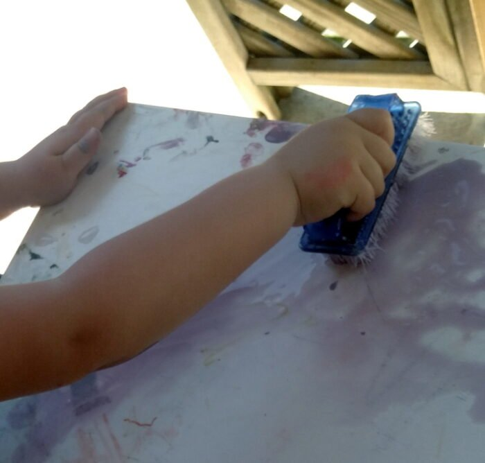Child washing a table.