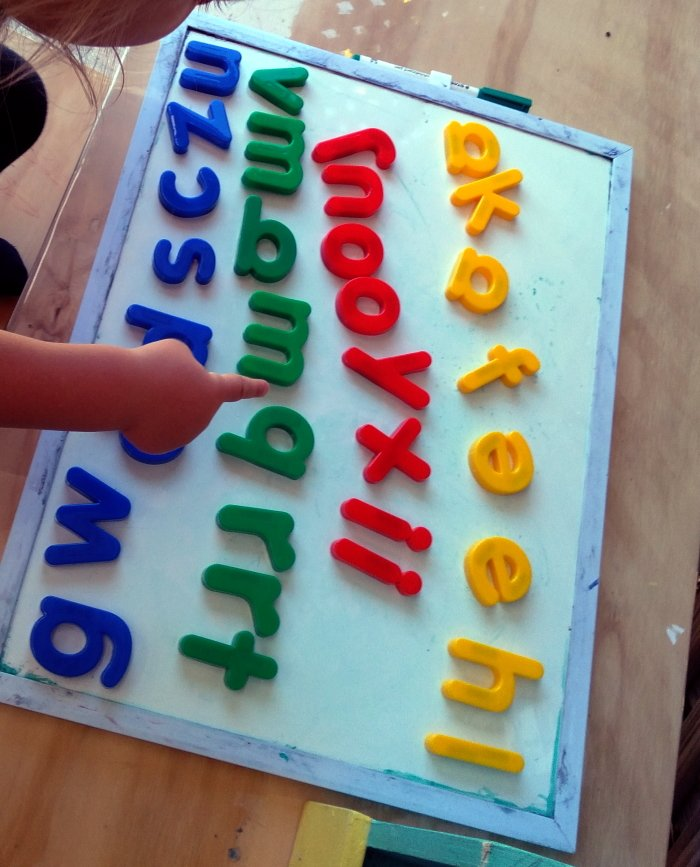 A white board with colorful magnetic letters