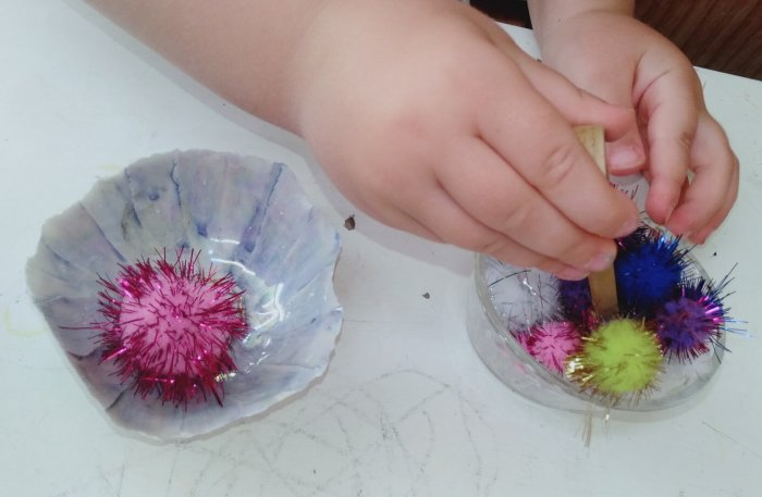 Child transferring pom poms from one small bowl into another.