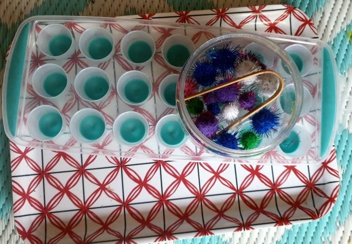 A tray with tweezers, pom poms in a jar.