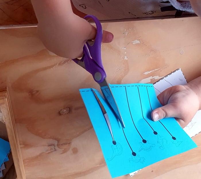 A child cutting blue paper with scissors
