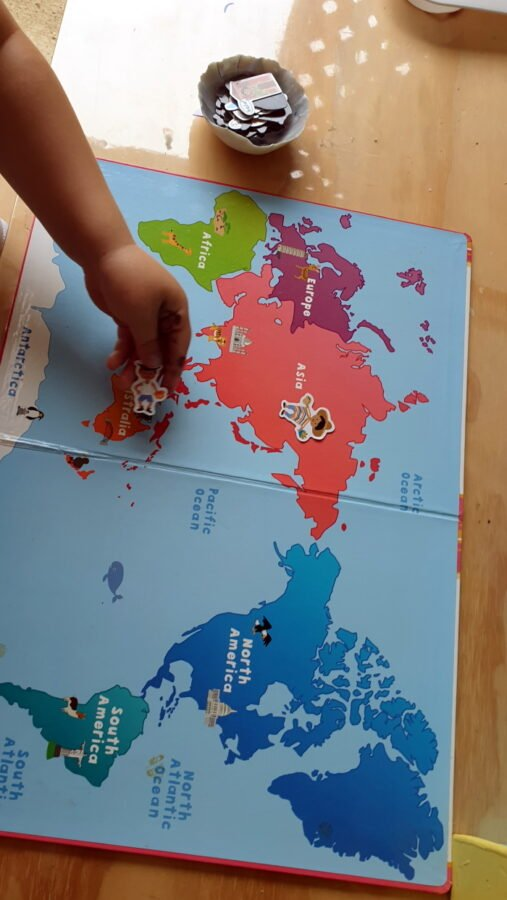 A child placing magnetic pieces on the magnetic world map