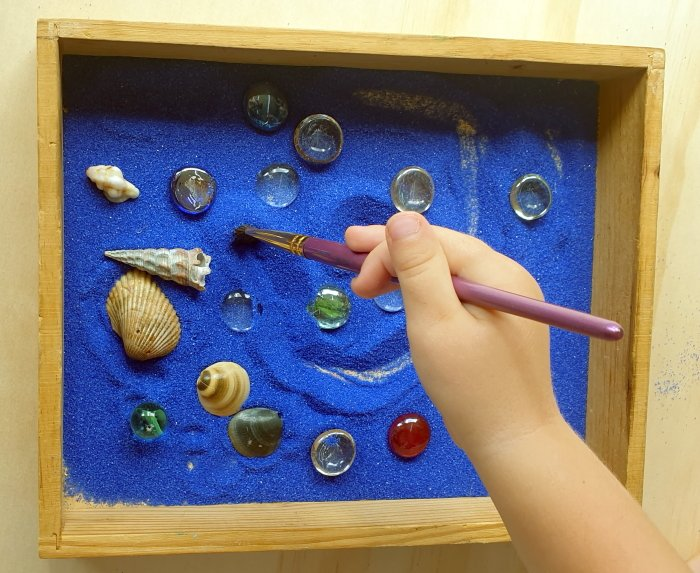 A child making strokes on sand in a tray around loose parts and shells
