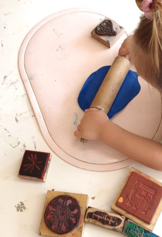 A child pressing rolling pin against playdough