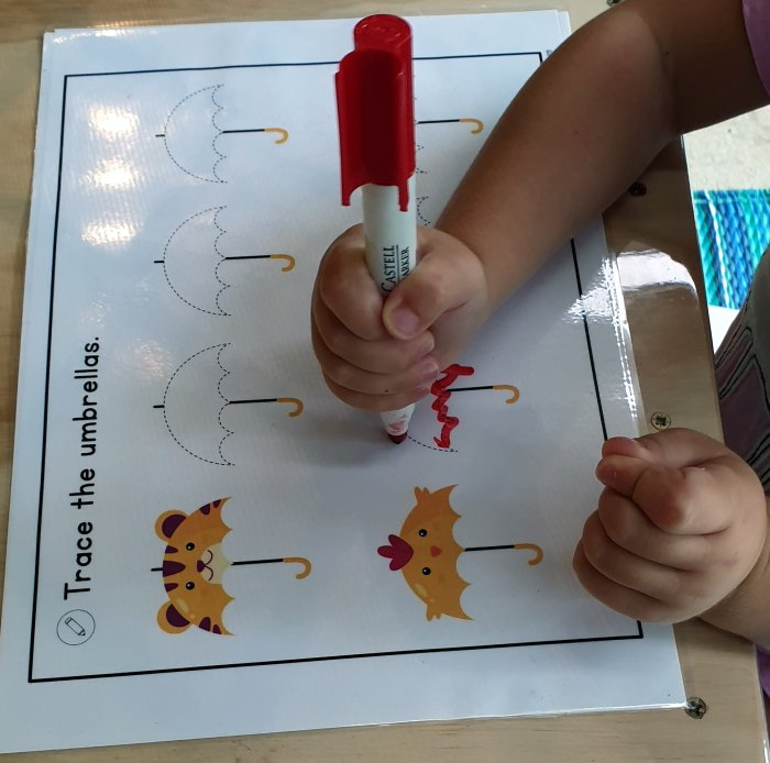 A child doing tracing activity with umbrellas