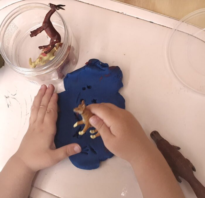 A child making prints with animal toys on playdough