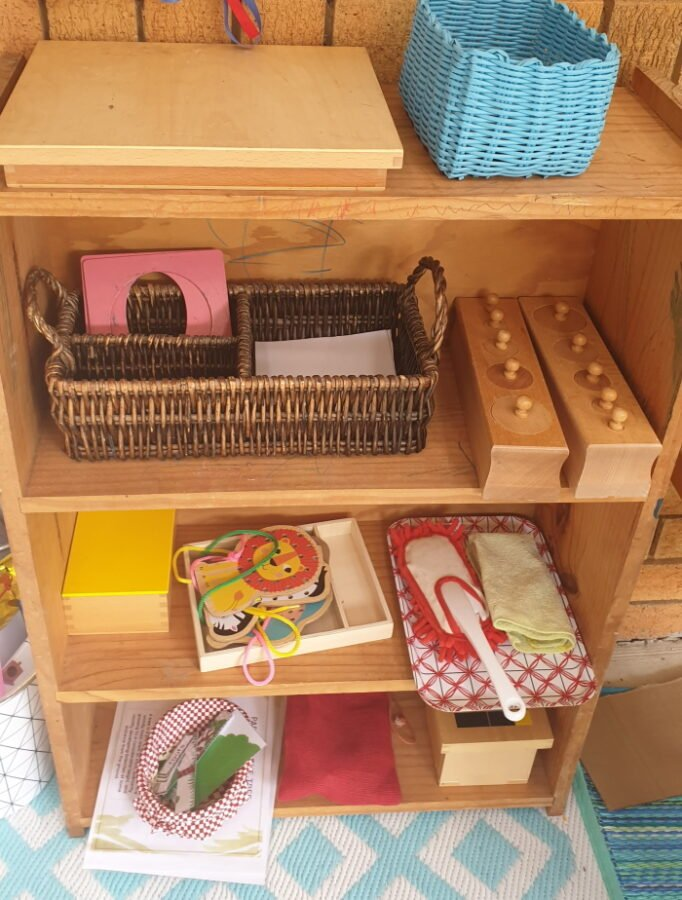 A wooden shelf with Montessori and learning activities for preschool children