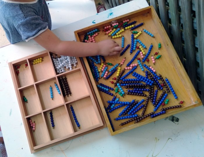 A child sorting beads by color and size