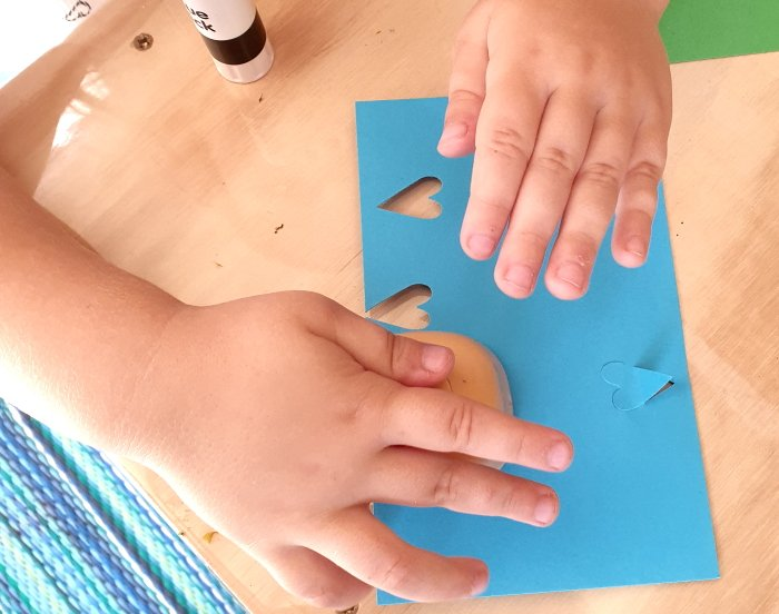 A child punching love hear shaps with construction paper
