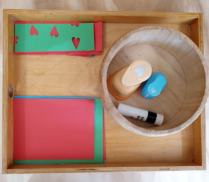 A tray with construction pieces of paper and shape punchers, glue stick.