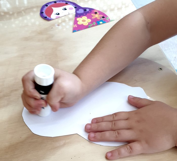 A child applying glue with a glue stick on a paper doll