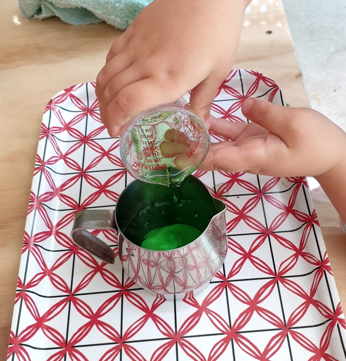Child pouring water into a jar from a measuring cup