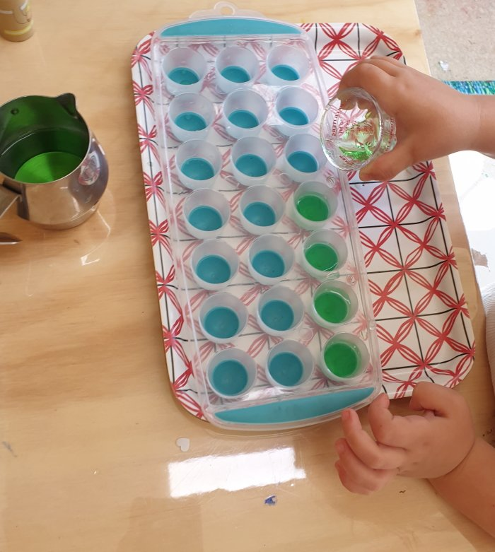 Child pouring water into an ice conteiner from a measuring cup