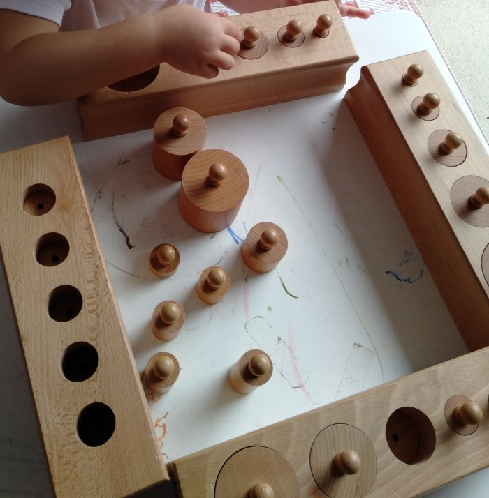 A child doing cylinder blocks and placing cylinders in the correct block.