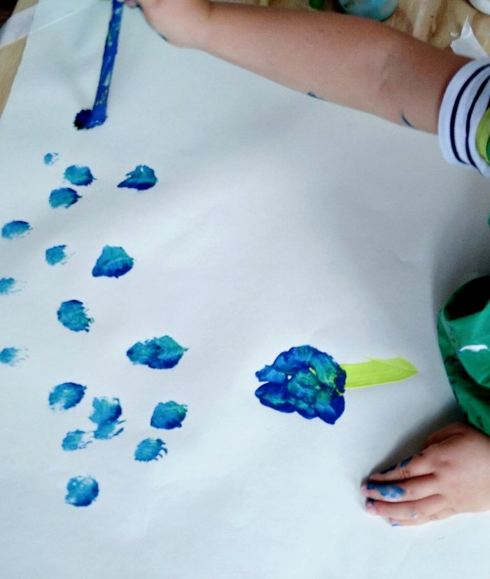 A child doing a painting with blue paints
