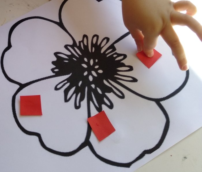 A child doing Anzac Day paper craft