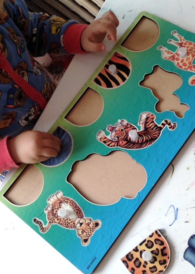 A child playing with an animal puzzle