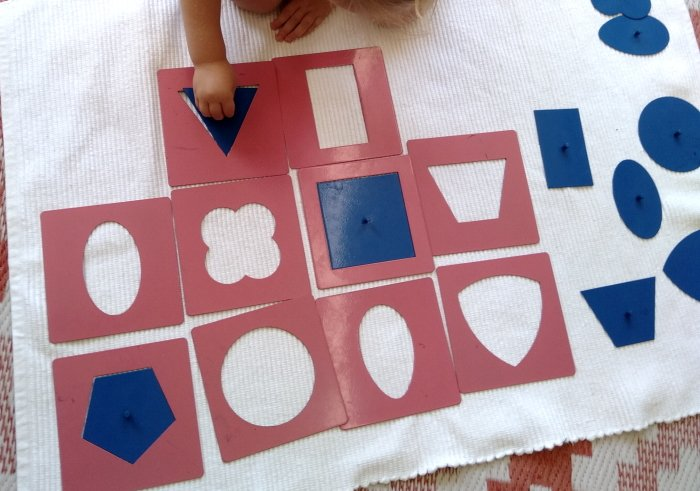 A child placing 2 d shapes into correct outline.
