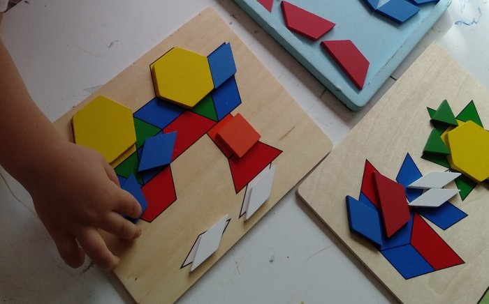 A child playing with shape matching wooden puzzle