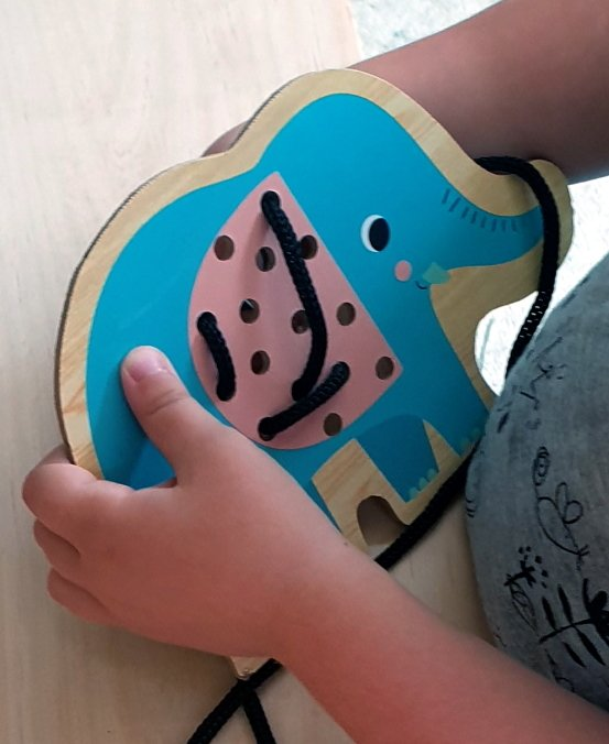 Child doing lacing with an elephant board