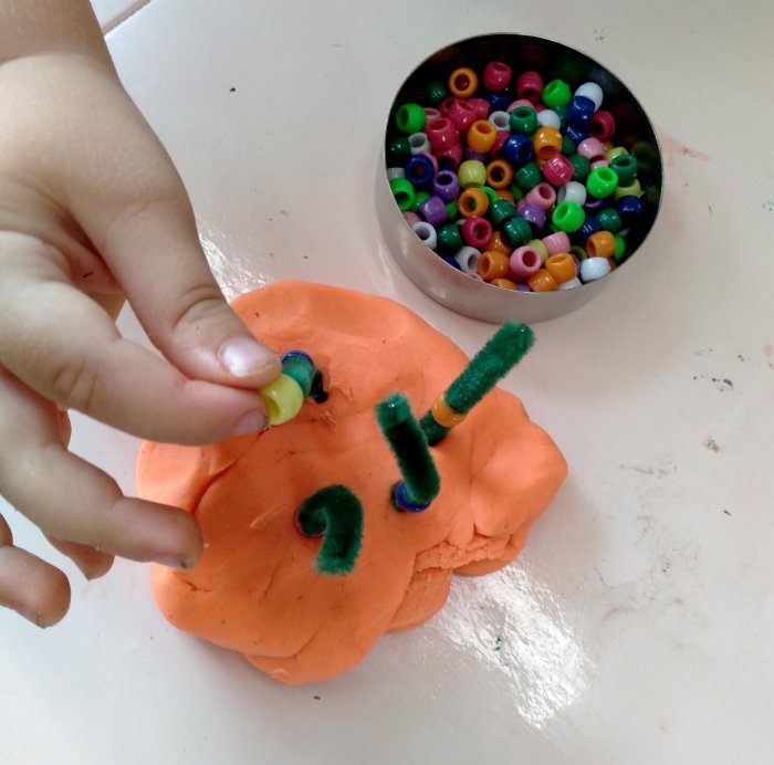 A child threading beads through pipe cleaners