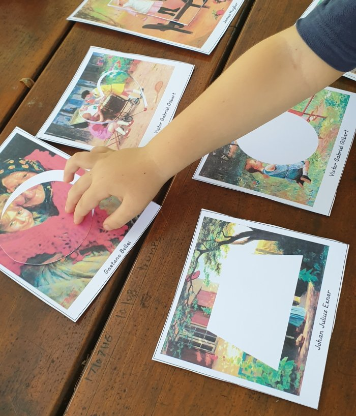 Child placing a round card on a picture card with famous paintings.