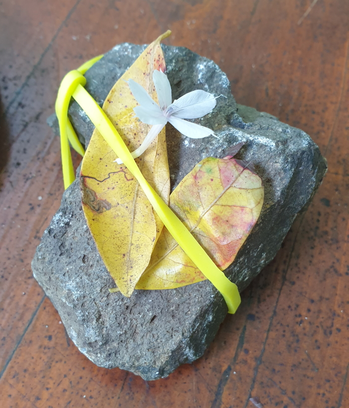 A craft with flower and rubber band tied around a rock