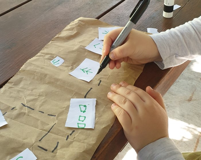 Child drawing a pathway on the handmade map.