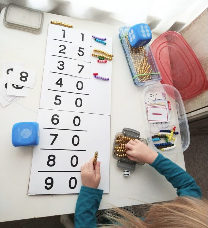 child counting tens with bead bars and seguin board