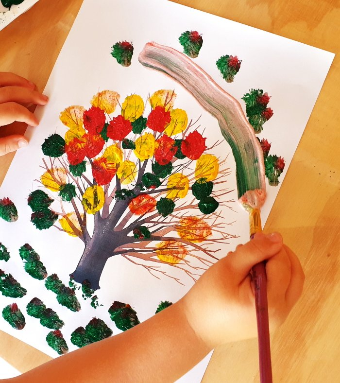 Child painting leaves on tree with paints