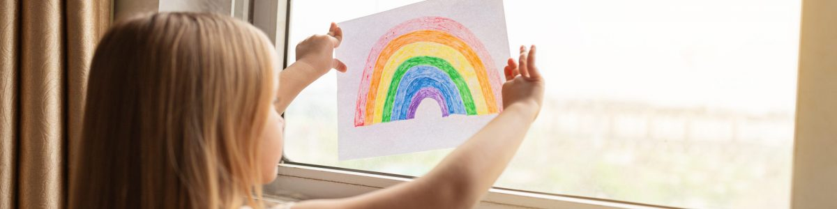 Kid painting rainbow during Covid-19 quarantine at home. Stay at home Social media campaign for coronavirus prevention, let's all be well, hope during coronavirus pandemic concept.
